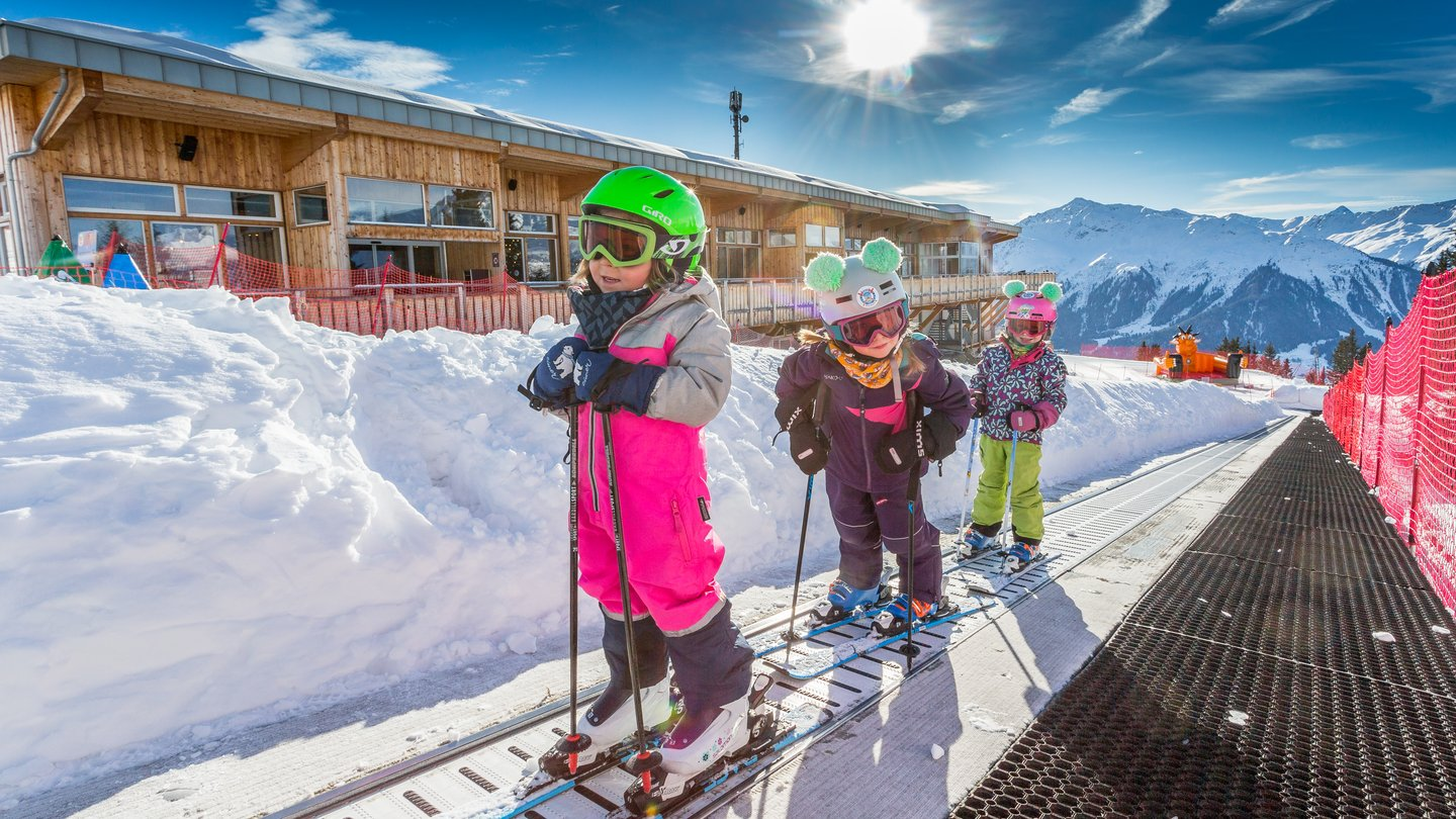 Four magic carpets transport children and beginner skiers on Madrisa in Klosters, Switzerland, back up the mountain after the first swings on snow.